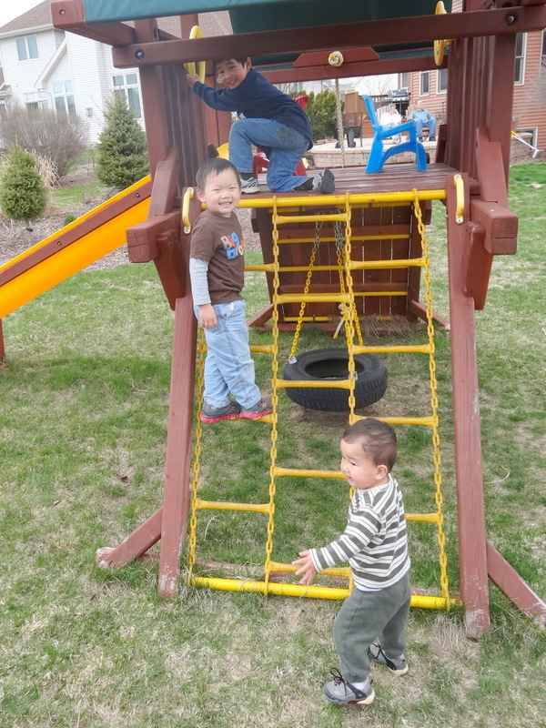 Michael teaching Max how to climb the playset lader.