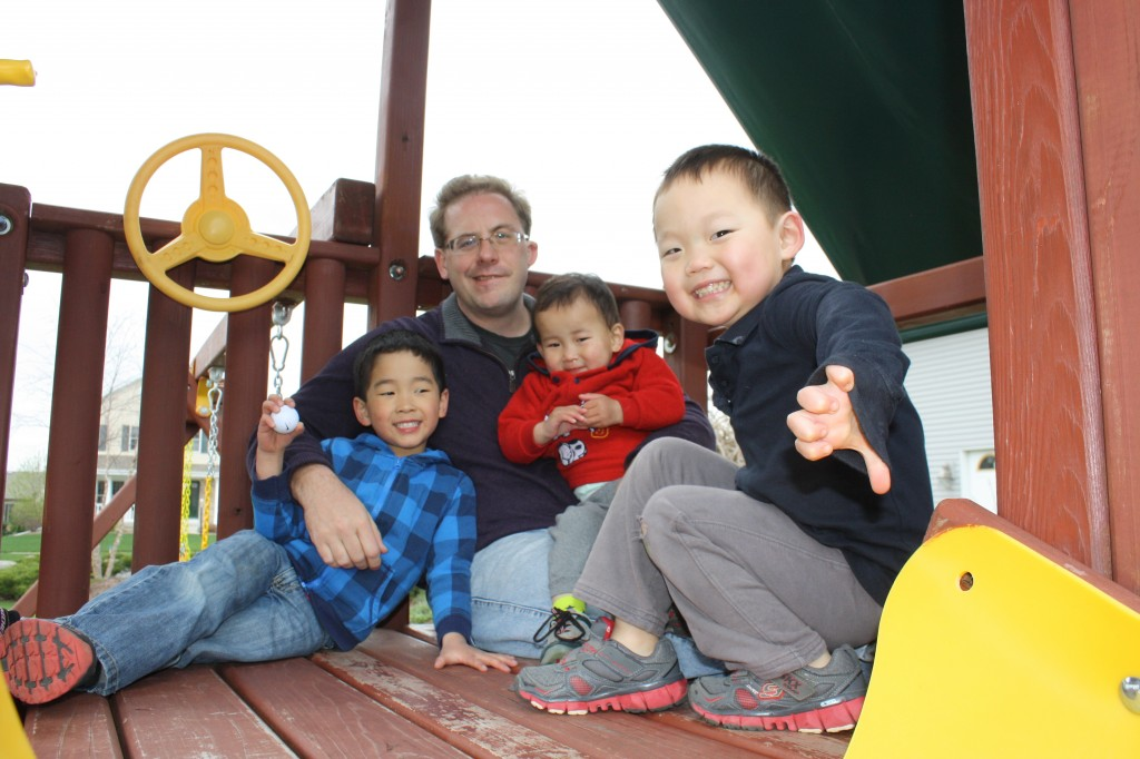 The four boys hanging out in atop the play set.